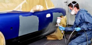 Man spray painting an auto collision repair