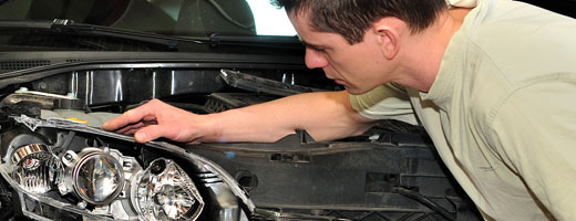 Man inspecting a car headlight system