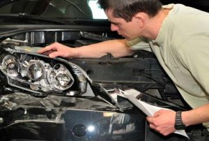 Autobody repair specialist inspecting a front panel and headlight